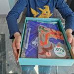 """enfant présentant les pièces du coffret d'activités """"Le monde des dinosaures"""""""