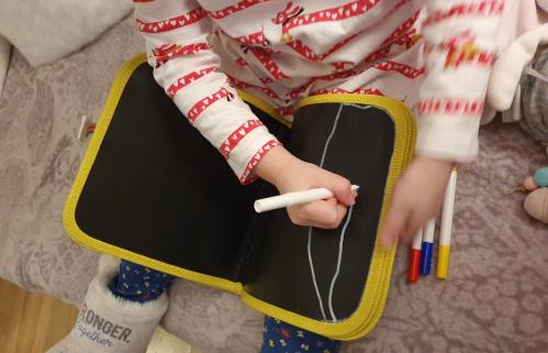 enfant dessinant sur ardoise de voyage moulin roty
